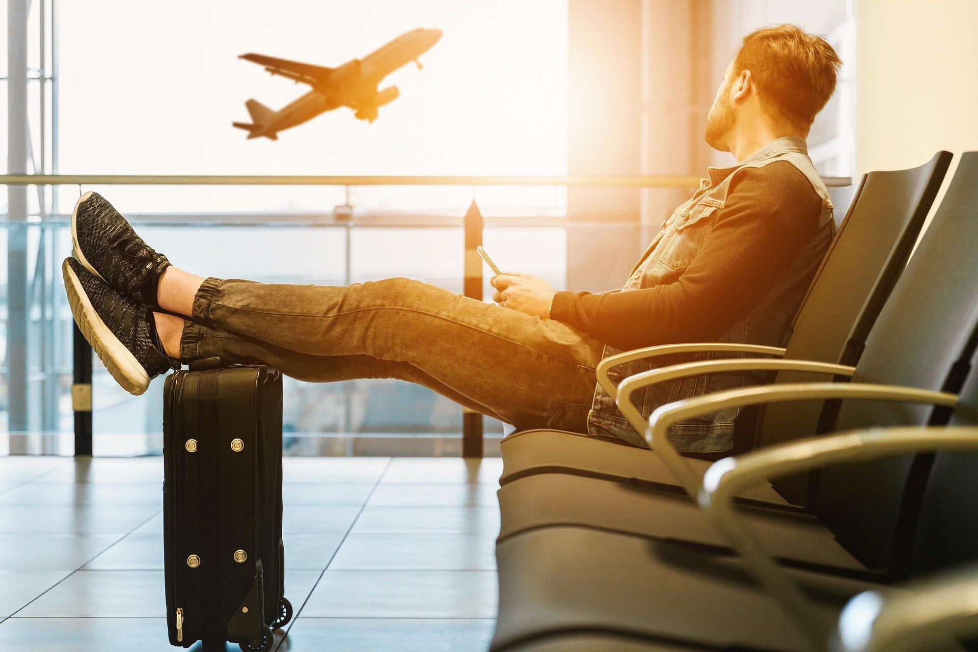 Homme attendant son vol dans un aéroport, les pieds sur sa valise cabine