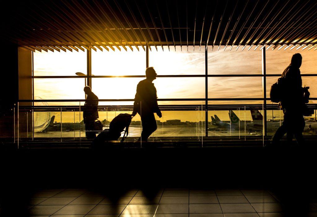 Des voyageurs roulent leur valise sur un tapis roulant dans un aéroport pour aller prendre leur avion