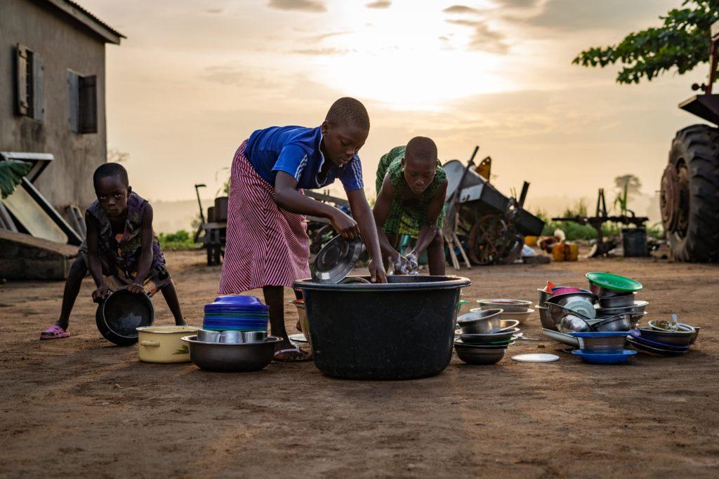 Des enfants font la vaisselle dans une bassine à Lomé au Togo