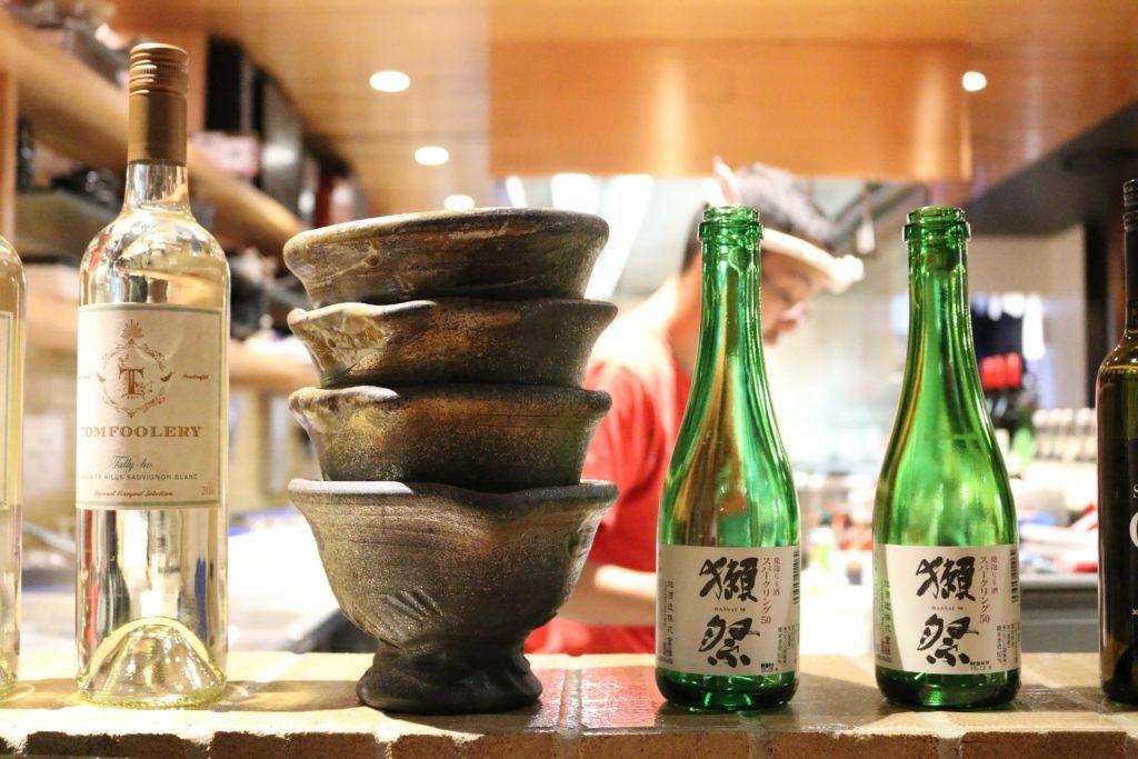 Bouteilles de vin et de saké avec coupes de saké
