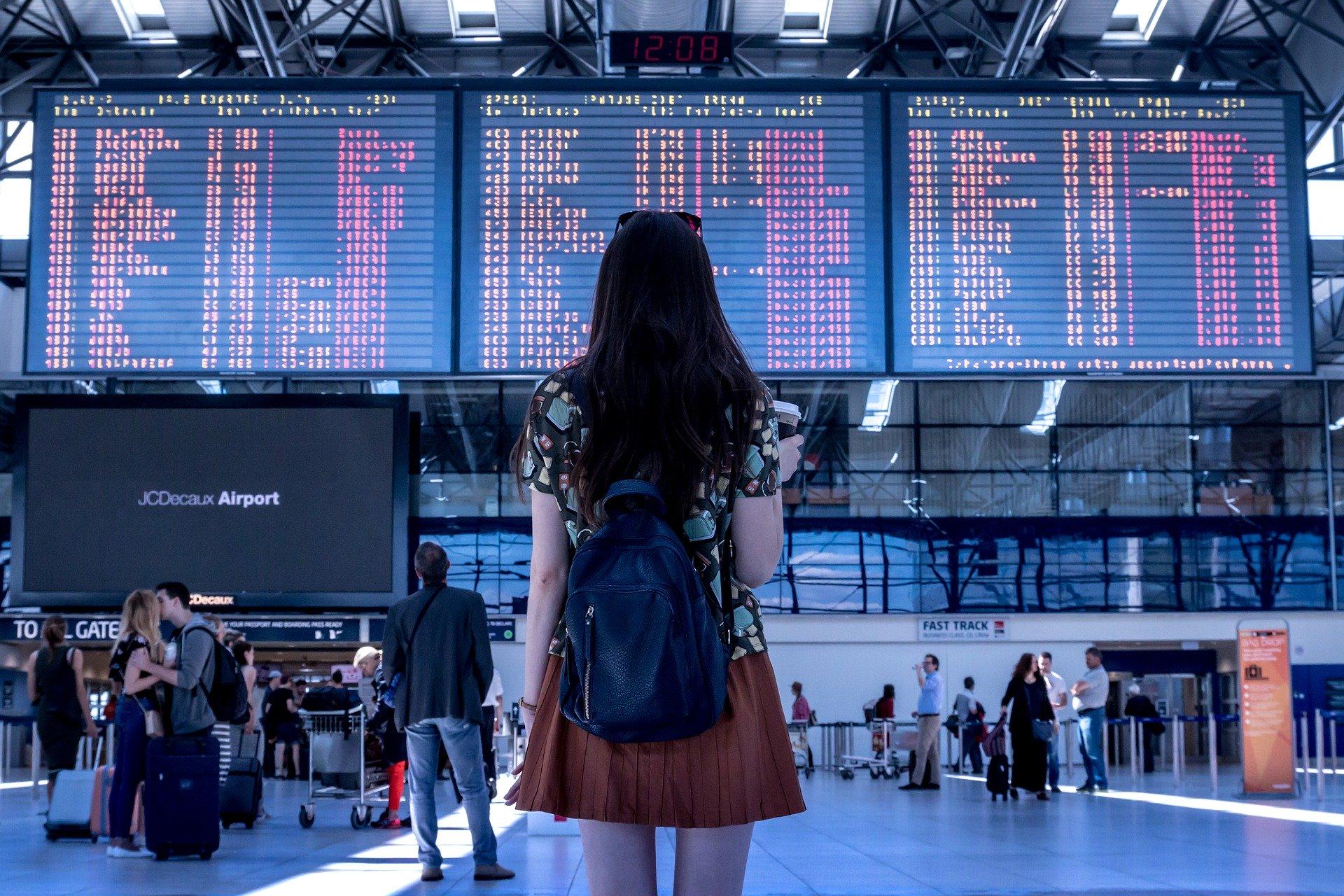 Voyageur dans un aéroport regardant le tableau des avions au départ