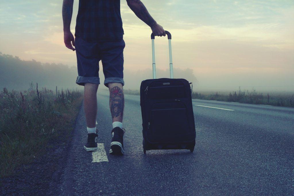 Un homme marche avec sa valise sur une route